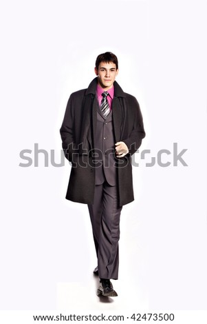 elegant young man in winter suit and coat studio on white