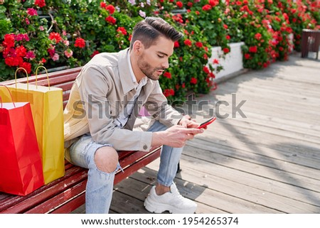 elegant young man sitting on a park bench with many flowers looking at his phone and with many colorful shopping bags next to him, shopping day. stock photo