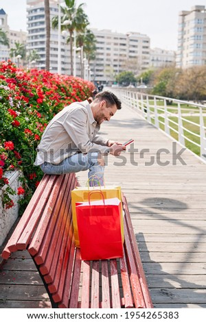 elegant young man sitting on a park bench with many flowers smiling looking at his phone and with many colorful shopping bags next to him, shopping day. stock photo