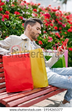 elegant young man sitting on a park bench with many flowers with a red phone and several shopping bags beside him stock photo