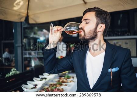 Elegant young man tasting wine