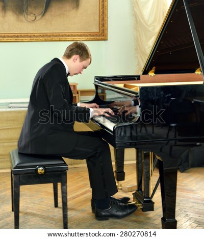 Elegant young pianist plays on black grand piano