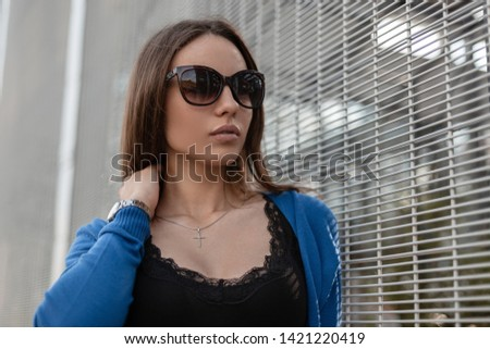 Elegant young pretty woman hipster in knitted blue cape in fashionable sunglasses in a black t-shirt is standing near a metal wall outdoors. Urban beautiful girl model model relaxes. Summer style.
