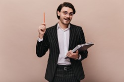 Elegant young teacher with brunette hair, in stylish light shirt, black striped suit, glasses holding writings, pen, and giving lecture. Man standing against beige background