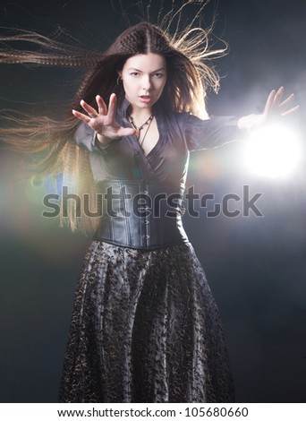 Elegant young witch in a dark clothes cast magic spell