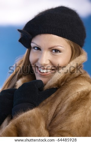 Elegant young woman dressed up warm in fur coat, cap and gloves, enjoying wintertime, smiling.?