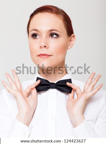 elegant young woman holding her bow tie and looking away