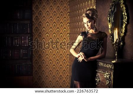 Elegant young woman in black evening dress posing in vintage interior. Fashion shot. #226763572