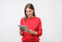 Elegant young woman in red sweater using tablet, looking at screen. Use modern technologies in common everyday life