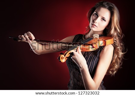 Elegant  young woman playing her violin with expression.