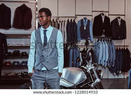 93538778 Elegantly dressed African American young man posing near retro sports  motorbike at the men's clothing store