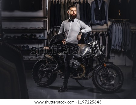 Elegantly dressed tattooed male with stylish beard holds black leather jacket posing near retro sports motorbike at the men's clothing store. #1197225643
