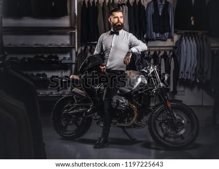 Elegantly dressed tattooed male with stylish beard holds black leather jacket posing near retro sports motorbike at the men's clothing store. #1197225643