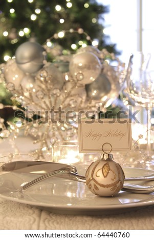 Elegantly lit holiday dinner table with focus on place card