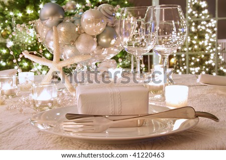 Elegantly lit  holiday dinner table with wine glasses and white ribbon gift