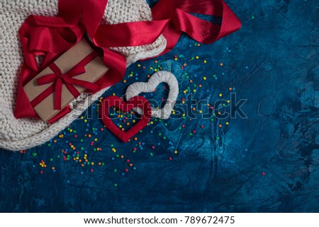 Element of Knitted Fabric, Red Ribbon, Gift in Kraft Paper with Red Ribbon, White and Red Heart on a blue background with different colors Konfeti. Stok fotoğraf ©