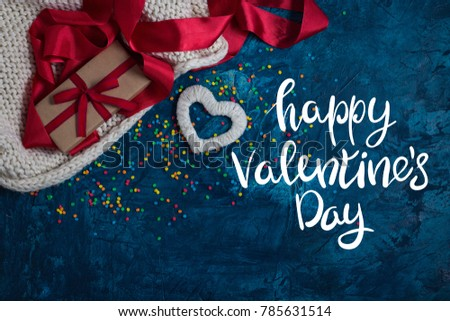Element of Knitted Fabric, Red Ribbon, Gift in Kraft Paper with Red Ribbon, White Heart on a blue background with multicolored, bright Konfeti. Added Text Happy Valentine's Day. Stok fotoğraf ©