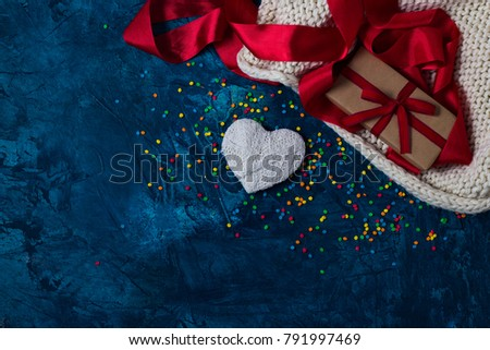Element of Knitted Fabric, Red Tape, Gift in Craft Paper With Red Ribbon, White Heart on a blue background with multicolored, bright Konfeti. Stok fotoğraf ©