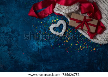 Element of Knitted Fabric, Red Tape, Gift in Kraft Paper with Red Ribbon, White Heart on a blue background with different colors Konfeti. Stok fotoğraf ©