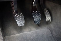 Element of modern luxury car interior metal gas clutch and brake pedal. Sport car with manual gearbox controls.