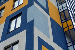 Element of the facade of a modern European building. The facade is painted with multi-colored geometric shapes