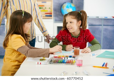 Elementary age children sitting around desk enjoying painting with colors in art class at primary school classroom.?