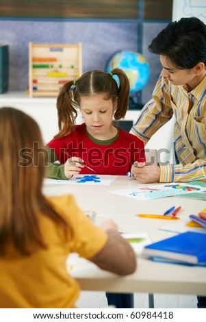 Elementary age children sitting around desk enjoying painting with colors in art class in primary school classroom.?