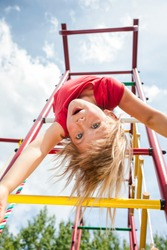 Elementary age girl hanging from a jungle gym (monkey bars or climbing frame) while playing in a playground - child safety or risky play concept
