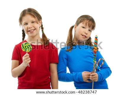 Elementary age girls smiling at camera holding lollipops in hands.