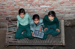 Elementary age School Girls sitting at home near brick wall on Charpai (domestic bed) holding chalkboard wearing school uniform and looking to the camera portrait close up