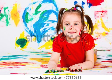 Elementary aged girl lying on the colored background