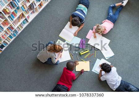 Elementary children lying on the floor and drawing at library.Top view of five multiethnic boys and girls in daycare house drawing on copybook. High angle view of group of kids with colorful pencils.