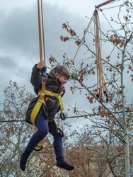 Elementary girl in a coat swinging on rubber bands at a city funfair on a cloudy autumn day