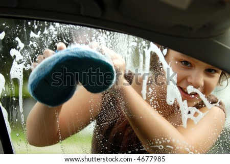 Elementary girl washing a car window viewed from inside the car. - stock photo