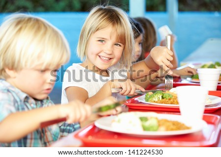 Elementary Pupils Enjoying Healthy Lunch In Cafeteria Photo stock ©