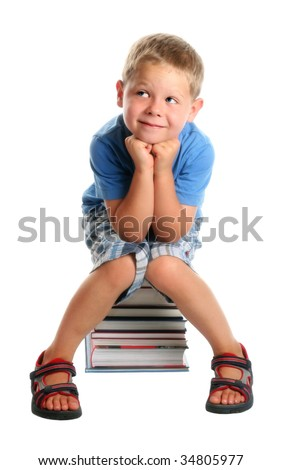 Elementary school age boy sitting on a pile of books, smiling. Isolated on white.