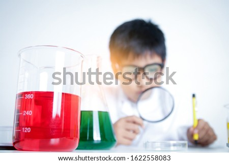 Elementary school boy wearing white dress, doing scientific experiments in the laboratory. Concepts of child education development
