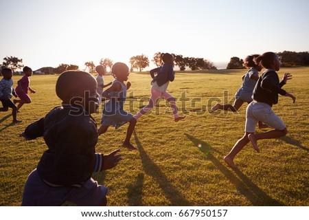 Elementary school boys and girls running in an open field