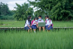 Elementary school children Asians living in rural areas Wear a face mask to prevent the coronavirus (COVID 19) in a rural school in Thailand. Students are studying online with friends.