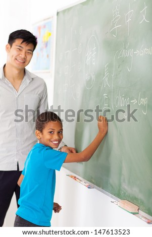 elementary school chinese language teacher and student in front of chalkboard