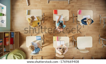 Elementary School Classroom: Children Sitting at their School Desk Working on Assignments in Exercise Notebooks.Top View Shot. Photo stock ©