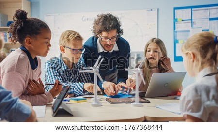 Elementary School Classroom: Enthusiastic Teacher Holding Tablet Computer Explains to a Brilliant Young Children How Wind Turbines Work. Kids Learning about Eco-Friendly Forms of Renewable Energy