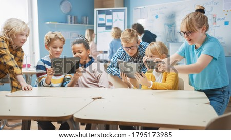Elementary School Computer Science Class: Children Use Digital Tablet Computers and Smartphones with Augmented Reality Software, They're Excited, Full of Wonder. Children in STEM, Playing and Learning