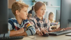 Elementary School Computer Science Classroom: Portrait of Smart Girl and Boy Talking while using Personal Computer, Learning Informatics, Internet Safety, Programming Language for Software Coding