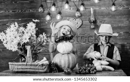 Elementary school fall festival idea. Autumn harvest festival. Children play vegetables pumpkin cabbage. Kids girl boy wear hat celebrate harvest festival rustic style. Celebrate fall traditions.