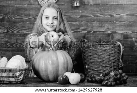Elementary school fall festival idea. Celebrate harvest festival. Kid girl fresh vegetables harvest rustic style. Child presenting harvest vegetable garden wooden background. Fall harvest holiday.