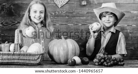 Elementary school fall festival idea. Celebrate harvest festival. Kids girl boy fresh vegetables harvest rustic style. Children presenting harvest vegetable wooden background. Fall harvest holiday.