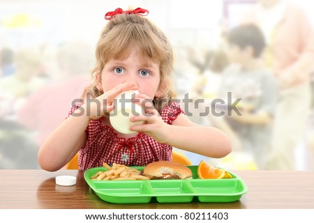 Elementary school girl child having cafeteria lunch at table.