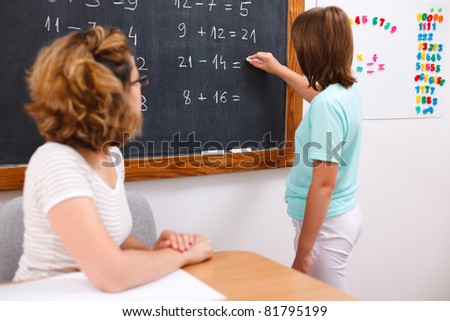 Elementary school girl writing equation solution on chalkboard, teacher looking at her (focus on black board)