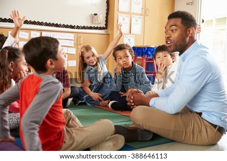 Elementary school kids and teacher sit cross legged on floor #388646113